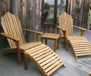 Pair of Teak Grand Adironack chairs with footrests on the patio